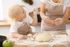 Bambina e la sua mamma bionda in grembiuli beige che giocano e che ridono mentre impastando la pasta nella cucina Homemad Fotografia Stock
