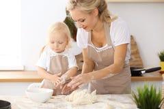 Bambina e la sua mamma bionda in grembiuli beige che giocano e che ridono mentre impastando la pasta nella cucina Homemad Fotografia Stock Libera da Diritti