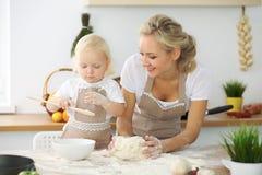 Bambina e la sua mamma bionda in grembiuli rossi che giocano e che ridono mentre impastando la pasta nella cucina Homemad Immagini Stock