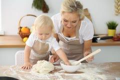 Bambina e la sua mamma bionda in grembiuli rossi che giocano e che ridono mentre impastando la pasta nella cucina Homemad Fotografia Stock Libera da Diritti