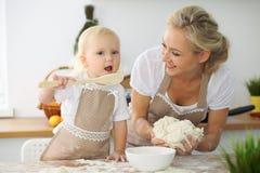Bambina e la sua mamma bionda in grembiuli rossi che giocano e che ridono mentre impastando la pasta nella cucina Homemad Fotografie Stock Libere da Diritti
