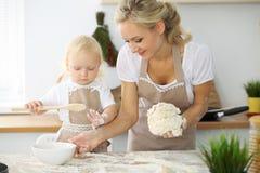 Bambina e la sua mamma bionda in grembiuli rossi che giocano e che ridono mentre impastando la pasta nella cucina Homemad Fotografie Stock