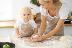 Bambina e la sua mamma bionda in grembiuli rossi che giocano e che ridono mentre impastando la pasta nella cucina Homemad Immagini Stock Libere da Diritti