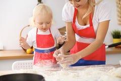 Bambina e la sua mamma bionda in grembiuli rossi che giocano e che ridono mentre impastando la pasta nella cucina Homemad Immagine Stock