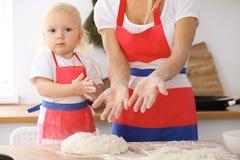Bambina e la sua mamma bionda in grembiuli rossi che giocano e che ridono mentre impastando la pasta nella cucina Homemad Immagine Stock Libera da Diritti