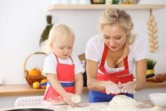 Bambina e la sua mamma bionda in grembiuli rossi che giocano e che ridono mentre impastando la pasta nella cucina Homemad Fotografia Stock
