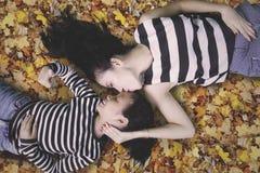 Bambina e mamma che si trovano sulle foglie di autunno Immagine Stock Libera da Diritti