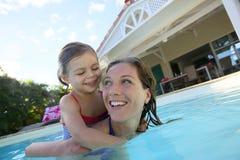 Bambina e sua madre nel divertiresi dello stagno Fotografie Stock Libere da Diritti