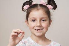 Bambina e un dente di latte fotografie stock libere da diritti