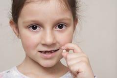 Bambina e un dente di latte fotografia stock