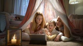 Bambina ed i suoi genitori che godono guardando i fumetti online nella tenda nella scuola materna archivi video