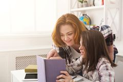 Bambina ed il suo libro di lettura della mamma a casa Immagini Stock