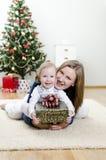 Bambina ed il suo regalo della holding della madre Immagini Stock