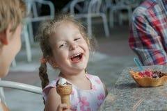 Bambina ed suo fratello del fratello germano che ridono durante il cibo del gelato italiano fotografia stock libera da diritti