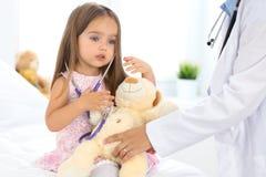 Bambina felice all'esame di salute all'ufficio di medico Concetto di sanità e della medicina fotografia stock