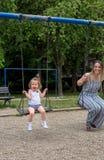 Bambina felice all'oscillazione del campo da giuoco Fotografie Stock Libere da Diritti