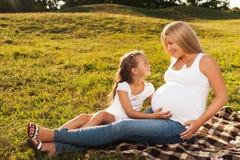 Bambina felice che abbraccia la pancia incinta di sua madre Fotografie Stock