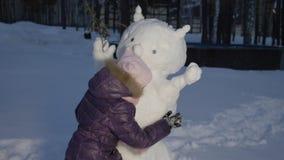 Bambina felice che abbraccia pupazzo di neve sull'inverno di sera che cammina nel villaggio del paese archivi video