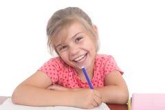 Bambina felice che fa compito Immagine Stock