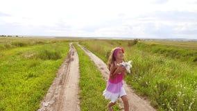 Bambina felice che gioca all'aperto sul prato, tramonto, estate modificato il bambino della ragazza funziona lungo il movimento l video d archivio