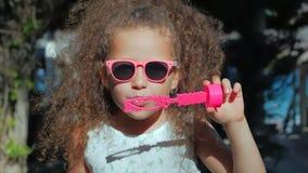 Bambina felice che gioca le bolle di sapone all'aperto e di salti, divertendosi sul cortile nave Bello bambino in parco archivi video