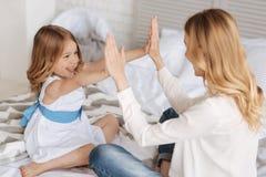 Bambina felice che gioca picchiettio-un-dolce con sua madre fotografia stock libera da diritti