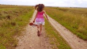 Bambina felice che gioca sul prato, tramonto, estate modificato il bambino della ragazza funziona lungo il video di movimento len video d archivio