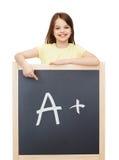 Bambina felice che indica dito la lavagna Immagini Stock