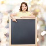 Bambina felice che indica dito la lavagna Fotografia Stock