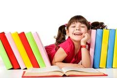 Bambina felice che legge un libro sul pavimento Immagine Stock
