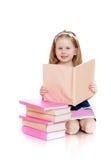 Bambina felice che legge un libro sulle sue ginocchia Immagine Stock