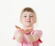 Bambina felice che raggiunge fuori le sue palme e che prende qualcosa Fotografie Stock