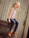 Bambina felice che si siede sul vecchio barilotto Immagine Stock
