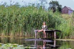Bambina felice che si siede sul vecchio molo di legno circondato dalle alte canne verdi che spruzzano acqua con i suoi piedi al g immagine stock libera da diritti
