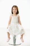 Bambina felice che si siede sulla presidenza Immagini Stock