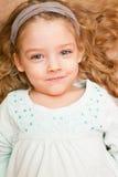 Bambina felice che si trova sul pavimento Immagine Stock