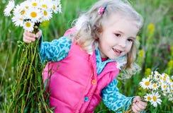 Bambina felice che tiene un mazzo delle margherite immagini stock libere da diritti