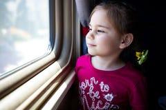 Bambina felice che viaggia in treno immagine stock