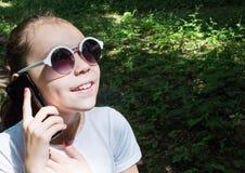 Bambina felice con gli occhiali da sole che esaminano il sole nella foresta di estate e che parlano sul dispositivo mobile fotografia stock