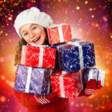 Bambina felice con i regali di Natale sul fondo delle luci Fotografia Stock