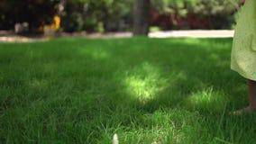 Bambina felice con il vestito giallo che corre a piedi nudi sull'erba verde nel parco video d archivio
