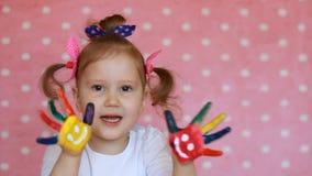 Bambina felice con le mani dipinte variopinte con i sorrisi su un fondo rosa Artista divertente del bambino con le palme sporche  video d archivio
