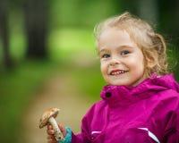 Bambina felice con un fungo Fotografia Stock Libera da Diritti