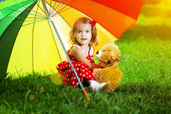 Bambina felice con un ombrello dell'arcobaleno in parco gioco del bambino Immagini Stock