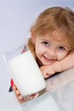 Bambina felice con un vetro di latte Fotografie Stock