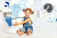 Bambina felice di divertimento del bambino per lavare i vestiti nella stanza di lavanderia immagini stock