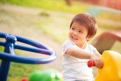 Bambina felice divertendosi su un godere del campo da giuoco immagine stock libera da diritti