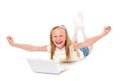 Bambina felice e sorridente con il computer portatile Immagine Stock