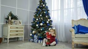 Bambina felice in pigiami che giocano con il coniglietto vicino ad un camino alla notte di Natale video d archivio