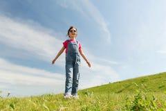 Bambina felice sopra il campo ed il cielo blu verdi Fotografie Stock Libere da Diritti